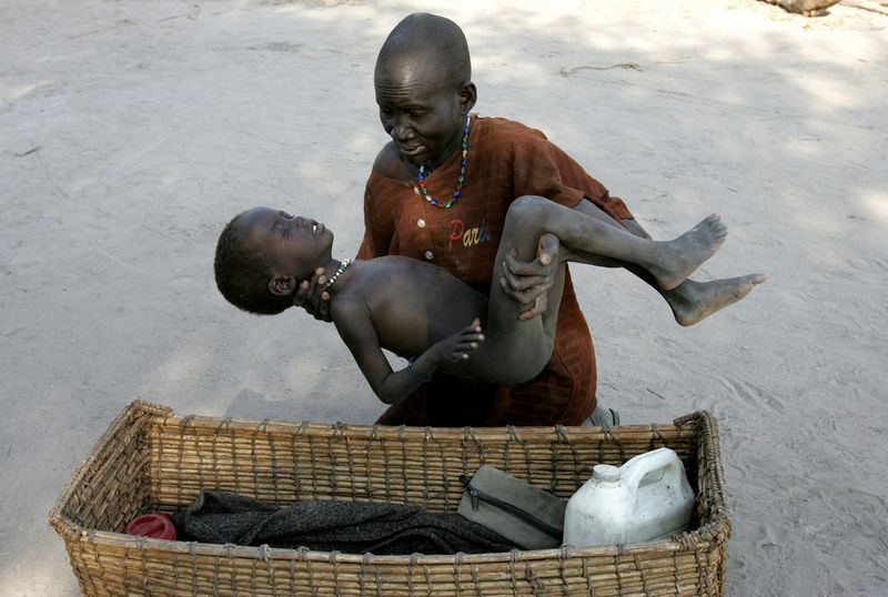 A moter gently place her son in a basket, Wednesday, Dec. 21, 2005 as she brought him to a MSF clinic in Lankien in Southern Sudan after he contracted malaria.