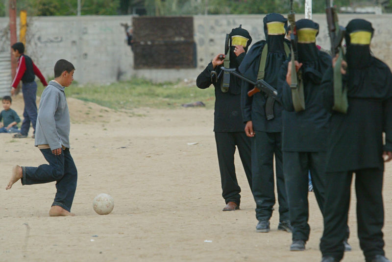 A Palestinian boy play soccer next to masked gunmen from the Palestinian Fatah movement,Tuesday, March 30, 2004 during a rally commemorating the 28th anniversary of Land Day in Nuseirat refugee camp in Gaza.