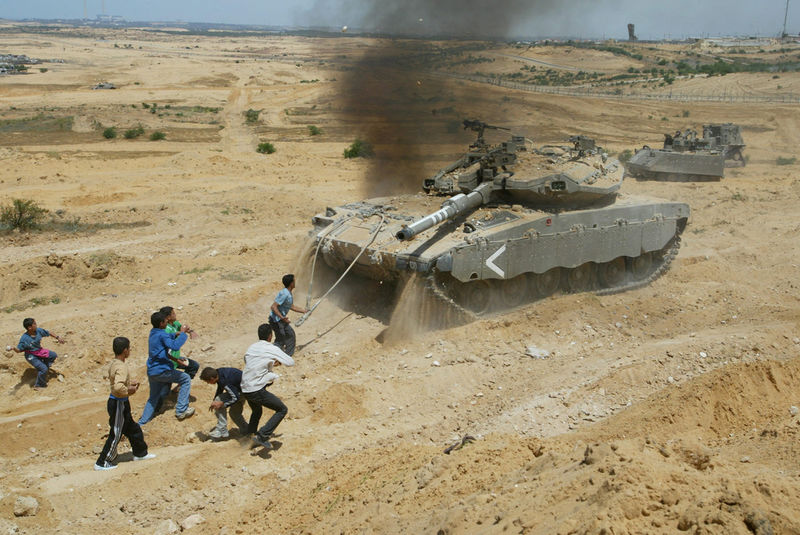 Palestinian boys throw stones towards a tank during clashes with Israeli soldiers, Tuesday, April 20, 2004 as Israeli tanks and a bulldozer raided an area near Nissanit in the Gaza strip .