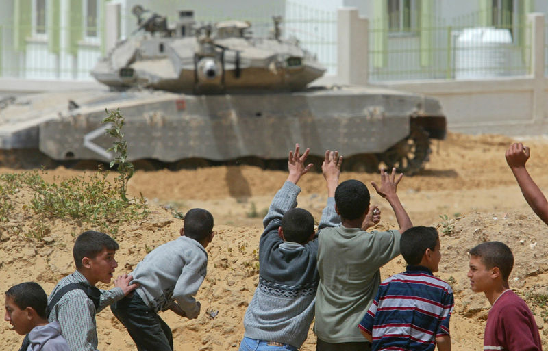 Palestinian youths react as a tank train its turret towards them, Wednesday, April 21, 2004 during clashes with Palestinians and the Israeli army in Beit Lahiya in the Gaza strip. Israeli forces backed by tanks and bulldozers raided a Gaza Strip town early Wednesday, killing at least four Palestinians, including two militants, in fighting with gunmen, Palestinian officials said.