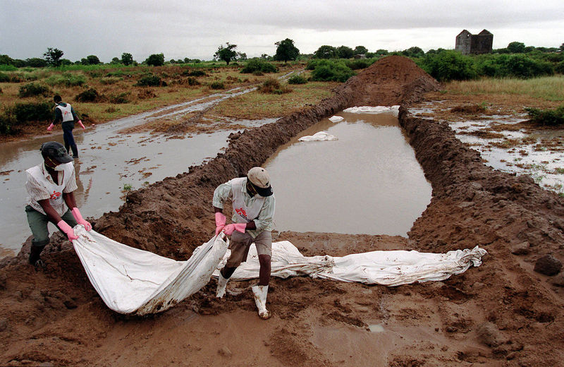 Local staff members of Doctors Without Borders carry corpses inside bodybags to a flooded mass grave in the outskirts of the town of Chokwe, 200 kilometers (125 miles) north of Maputo, Mozambique Thursday March 9, 2000. Heavy rains drenched flood-ravaged southern Mozambique, soaking hundreds of thousands of displaced people crammed into aid camps, hampering relief operations and raising fears of further flooding.
