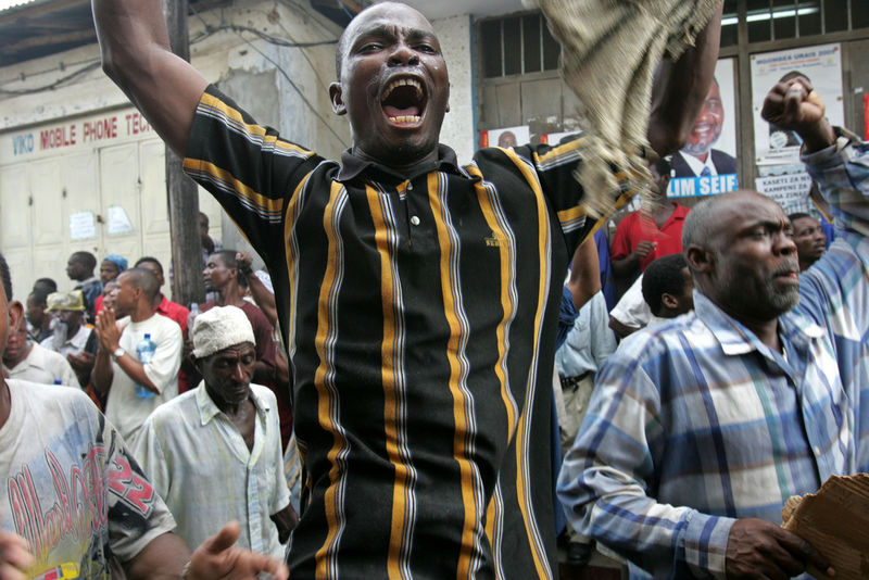 Civic United Front supporters scream as riot police fire teargas in Stone Town , Tuesday, Nov. 1, 2005 at the party headquaters in Zanzibar.Zanzibari police, backed by soldiers, surrounded the two main opposition party headquarters early Tuesday and marched into at least two other opposition neighborhoods, beating up protesters in a show of forces following disputed weekend elections.(