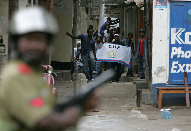 Memebers of the opposition Civic United Front  stand in an alley in Stone Town in Zanzibar, Monday, Oct. 31 as a riot police man look on.Riot police used tear gas and water cannon Monday to disperse opposition supporters celebrating what their leader called a clear early lead in returns from crucial elections on this semiautonomous archipelago
