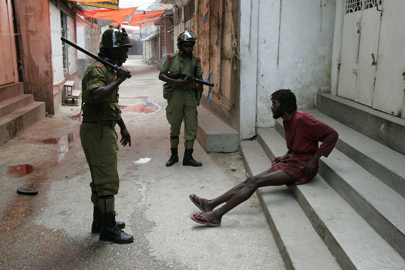 Riot police arrest a man suspected of being an opposition supporter, Monday, Oct. 31, 2005 in Stone Town in Zanzibar.Riot police used tear gas and water cannon Monday to disperse opposition supporters celebrating what their leader called a clear early lead in returns from crucial elections on this semiautonomous archipelago.