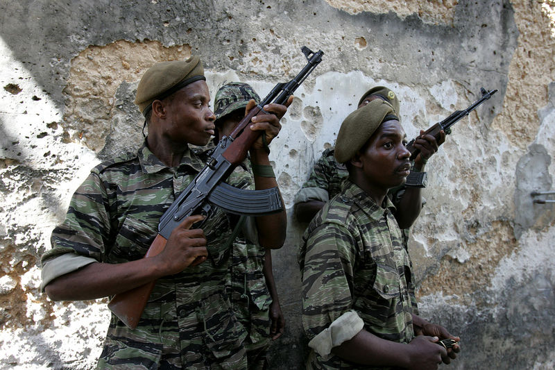 Members of the army take up positions as they prepare to fire on members of the opposition who is trying to prevent people from outside the area from voting in Stone Town in Zanzibar, Sunday, Oct. 30, 2005. The people were brought in on trucks by police to vote in an opposition stronghold.Tensions were high on the Indian Ocean island of Zanzibar as voters chose Sunday between the socialists who have ruled the semiautonomous state for more than 30 years and an opposition group promising wholesale change.