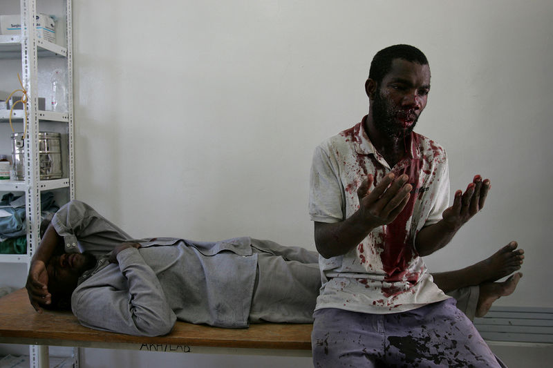 A man pray in hospital after he and the man on the stretcher were beaten , Sunday, Oct. 30, 2005 by ruling party militias in Zanzibar.Tensions were high on the Indian Ocean island of Zanzibar as voters chose Sunday between the socialists who have ruled the semiautonomous state for more than 30 years and an opposition group promising wholesale change.