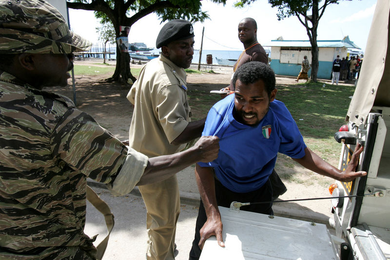 Members of the army and police arrest a opposition member who is tried to prevent people from outside the area from voting in Stone Town in Zanzibar, Sunday, Oct. 30, 2005. The people were brought in on trucks by police to vote in an opposition stronghold.Tensions were high on the Indian Ocean island of Zanzibar as voters chose Sunday between the socialists who have ruled the semiautonomous state for more than 30 years and an opposition group promising wholesale change.(