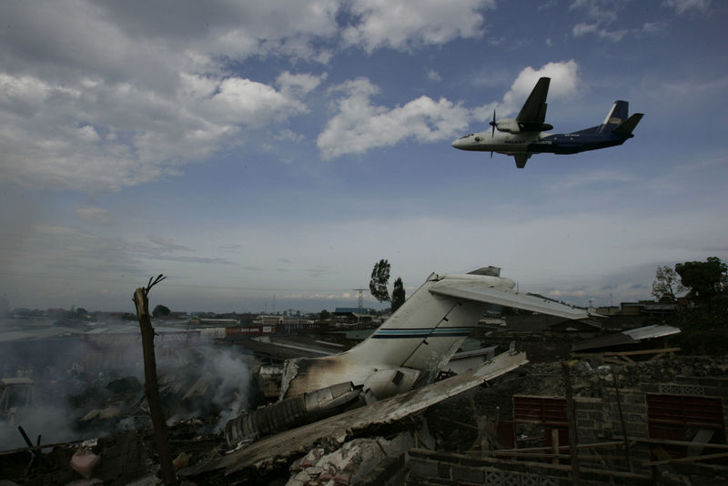 A plane take of from the runway at Goma airport,Wednesday, April 16, 2008 with the wreckage od a Congolese jetliner lying bellow.