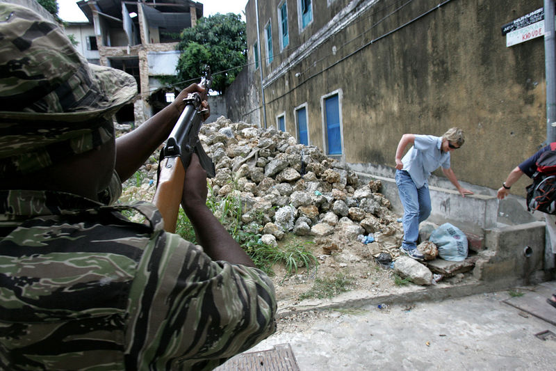 Tourist run to saftey as members of the army and police fire on members of the opposition , Sunday, Oct. 30, 2005 who is trying to prevent people from outside the area from voting in Stone Town in Zanzibar. The people were brought in on trucks by police to vote in an opposition stronghold.Tensions were high on the Indian Ocean island of Zanzibar as voters chose Sunday between the socialists who have ruled the semiautonomous state for more than 30 years and an opposition group promising wholesale change.