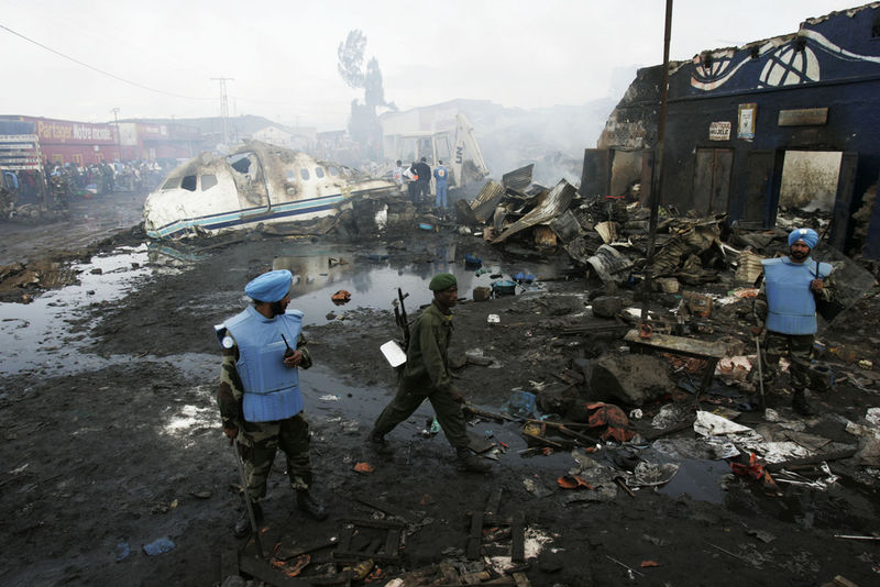 A Congolese soldier and UN Indian soldiers guard the wreckage, Wednesday, April 16, 2008 of a Congolese jetlainer that carshed on takeoff in Goma.