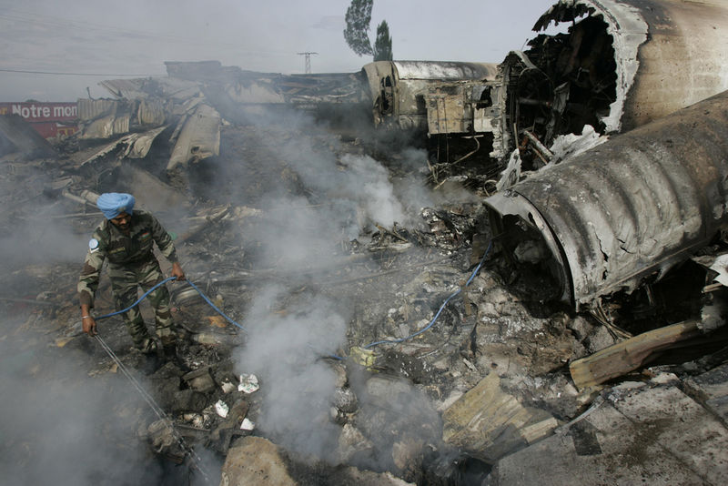 An Indian UN soldier try to extinguish the smouldering wreckage, Wednesday, April 16, 2008 of a Congolese jetlainer that carshed on takeoff in Goma.
