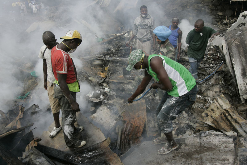 Congolese volunteers try to extinguish the smouldering wreckage, Wednesday, April 16, 2008 of a Congolese jetlainer that carshed on takeoff in Goma.