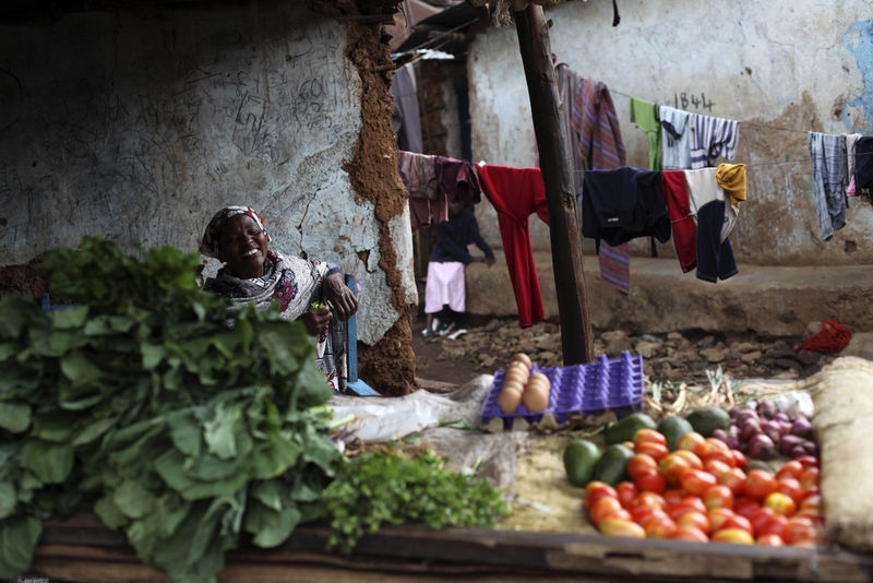 A woman selling vegetables laugh as she speak to customers, not seen,Wednesday, May 27, 2009 in the Kibera slum in Nairobi, Kenya.Kibera in Nairobi, Kenya is the largest slum in Africa, and has a population estimated at one million