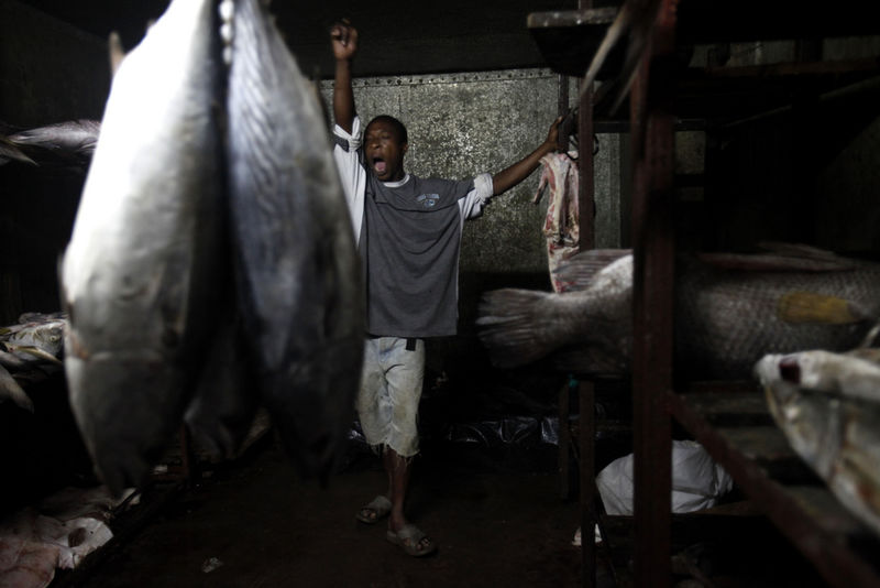 In this Tuesday, Nov. 24, 2009 picture A Kenyan fishermen yawn in a freezer packed with fish in Malindi.Fishermen who fish for a living and sportsmen who catch fish for fun say they've seen a rise in fish stocks in northern Kenya and suspect the rise is due to Somali pirates who have forced commercial trawlers off the Somali coast.(