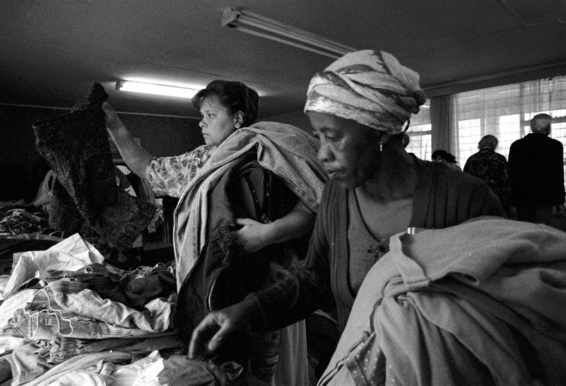 Balck and white people look for clothes handed out by church, Gauteng 1998