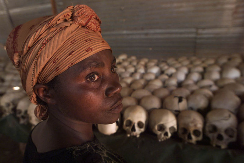 Dancila Nyirabazungu, 50, standing in front of skeletal remains of victims of Rwanda's 1994 genocide preserved where they were killed at Ntarama's Roman Catholic Church on Monday, Oct. 1, 2001.