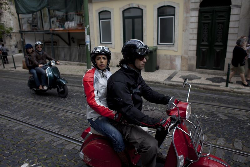Two couples ride on Vespa moto scooters, Saturday, April 9, 2011 through the streets of Lisbon, Portugal.(AP Photo/Karel Prinsloo)