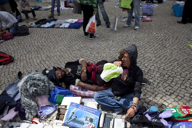 A woman drink from a container , Saturday, April 9, 2011 as they try to sell some goods at a flea market in Lisbon, Portugal.(AP Photo/Karel Prinsloo)