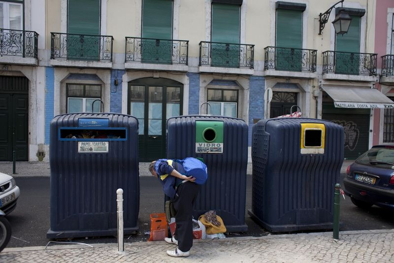 A man look through garbage left outside a recycling centre, Saturday, April 9, 2011 in downtown Lisbon, Portugal. (AP Photo/Karel Prinsloo)