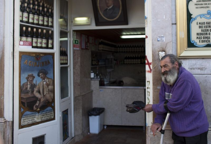 A man wait for customers outside a bar as he begs, Saturday, April 9, 2011 in downtown Lisbon, Portugal. (AP Photo/Karel Prinsloo)