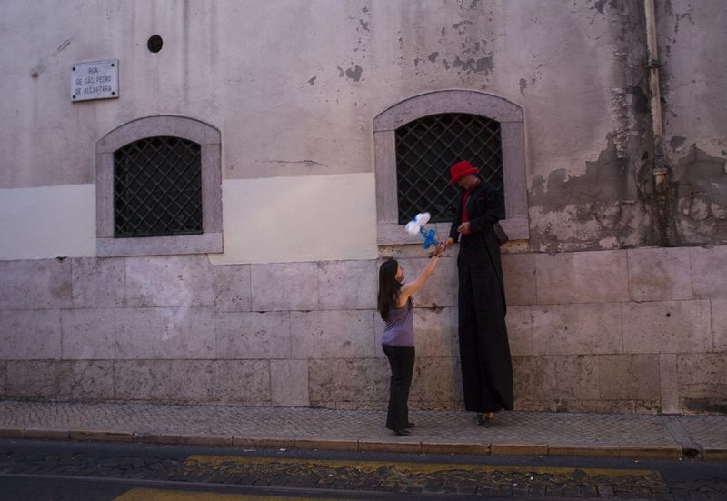 A performer walking on silts give a woman a balloon in a street, Saturday, April 9, 2011 in downtown Lisbon, Portugal. (AP Photo/Karel Prinsloo)