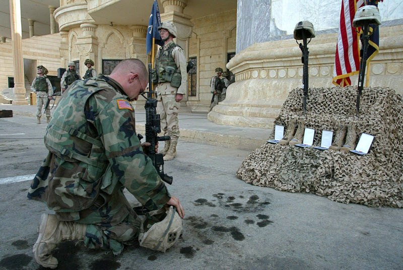 A U.S soldier kneel in front of Spc. Donald L. Wheeler and Spc. James Powell helmets placed together with their nametags over their rifle butts, Thursday, Oct 16, 2003 during a memorial ceremony in Tikrit after the two soldiers were killed in two seperate incidents earlier in the week.