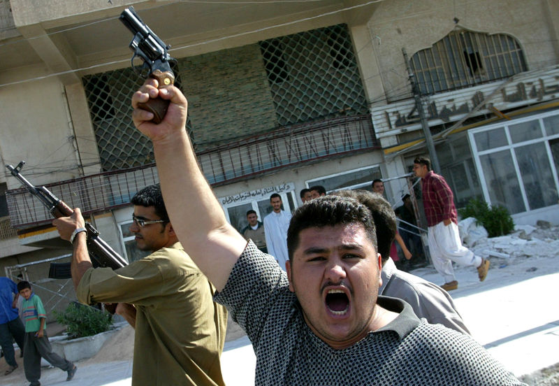 Iraqis scream as they fire into the air during the funeral of slain Iraqi policemen in Fallujah Saturday Sept. 13, 2003.