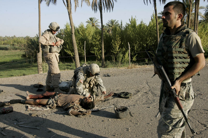 U.S soldiers from the 5th Squadron, 73rd Cavalry regiment, 3d Brigade combat team of 82nd Airborne Division treat an injured Iraqi soldier near the city of Baqouba, 60 kilometers (35 miles) northeast of Baghdad on Tuesday, Aug.28, 2007 after the Iraqi army hit an improvised explosive device.