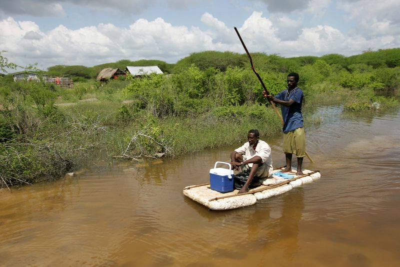 "Somali men use a piece of foam as they float in floodwaters near the village of Marere in southern Somalia, Tuesday, Nov.28, 2006 after the Juba river burst its banks. Fears of a looming war in Somalia are hampering relief efforts for up to one million people hit by severe flooding, a senior U.N. official said Friday. Eric Laroche, the U.N.'s humanitarian chief for Somalia, said a ""corridor of peace"" is needed so aid can reach 400,000 people who have fled their homes to escape the worst flooding in a decade.(AP Photo/Karel Prinsloo)"