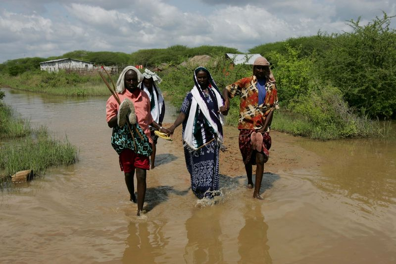"Somali men help a woman through floodwaters near the village of Marere in southern Somalia, Tuesday, Nov.28, 2006 after the Juba river burst its banks. Fears of a looming war in Somalia are hampering relief efforts for up to one million people hit by severe flooding, a senior U.N. official said Friday. Eric Laroche, the U.N.'s humanitarian chief for Somalia, said a ""corridor of peace"" is needed so aid can reach 400,000 people who have fled their homes to escape the worst flooding in a decade.(AP Photo/Karel Prinsloo)"