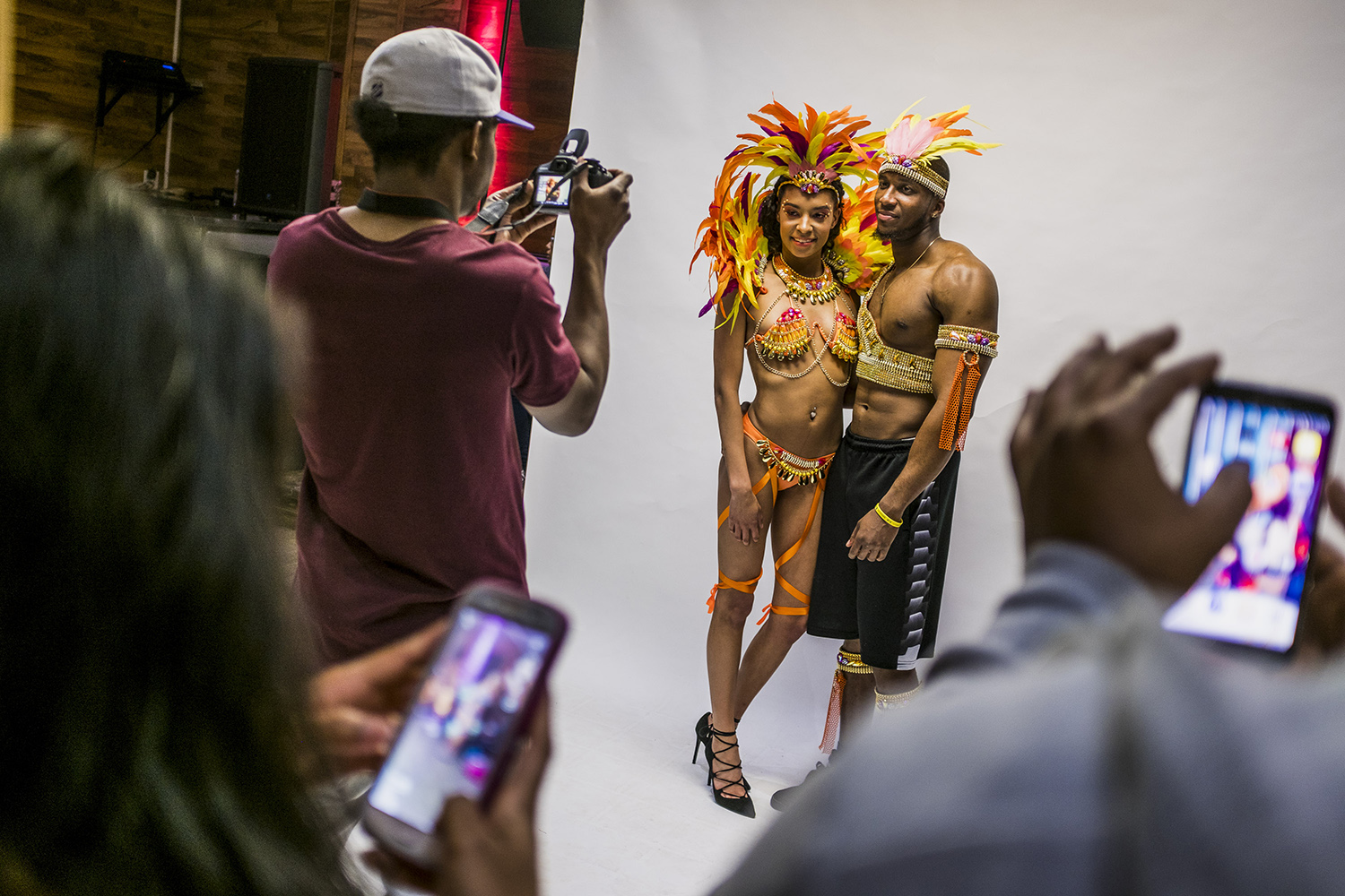 Masqueraders take part in a photo session with the new costumes they will be wearing during the Grand Parade.