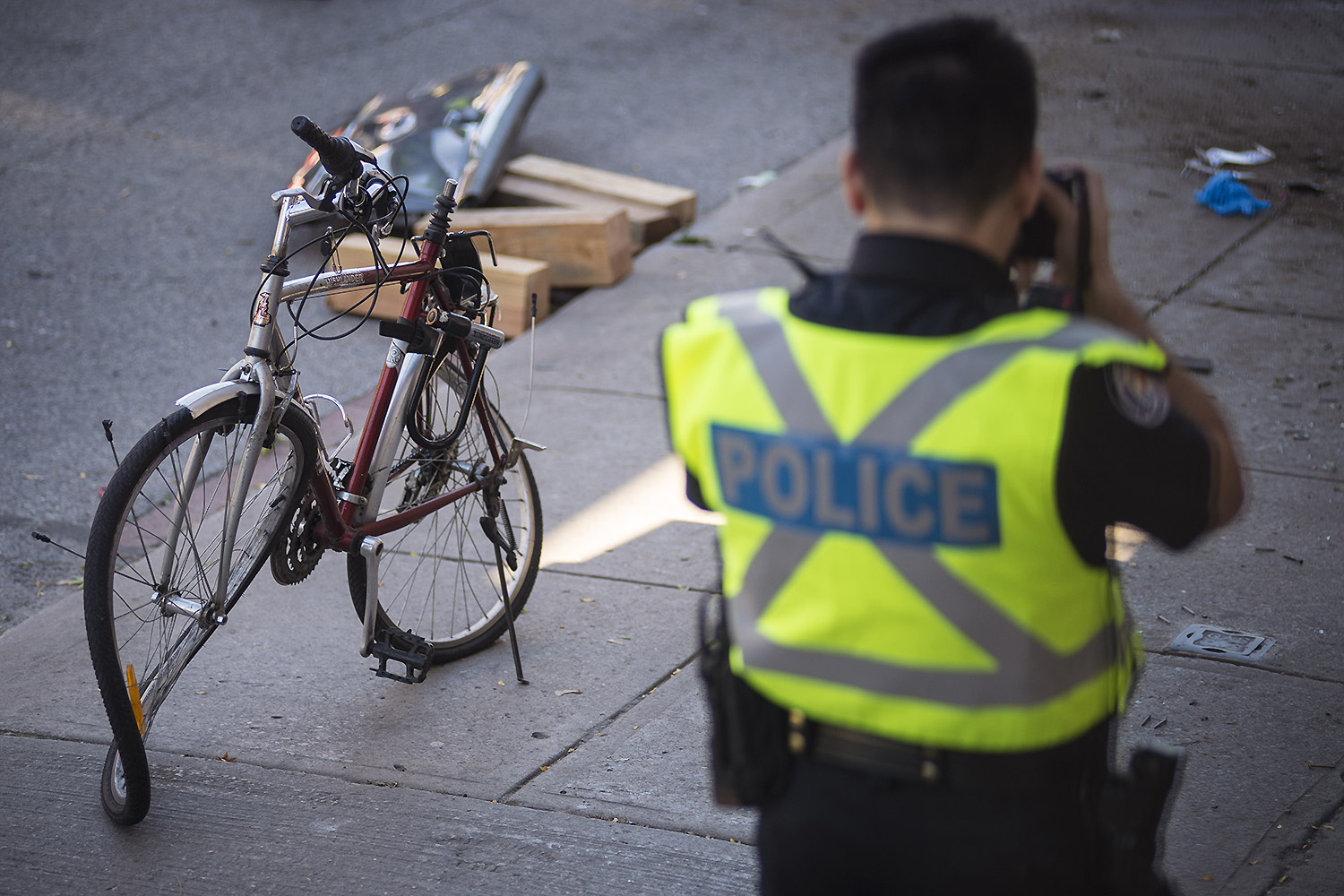 A police officer photographs the destroyed bike of David Delos Santos, 39, who died after he was struck by a vehicle that had crashed into a streetcar at King and Cowan Ave., Wednesday, October 18, 2017.