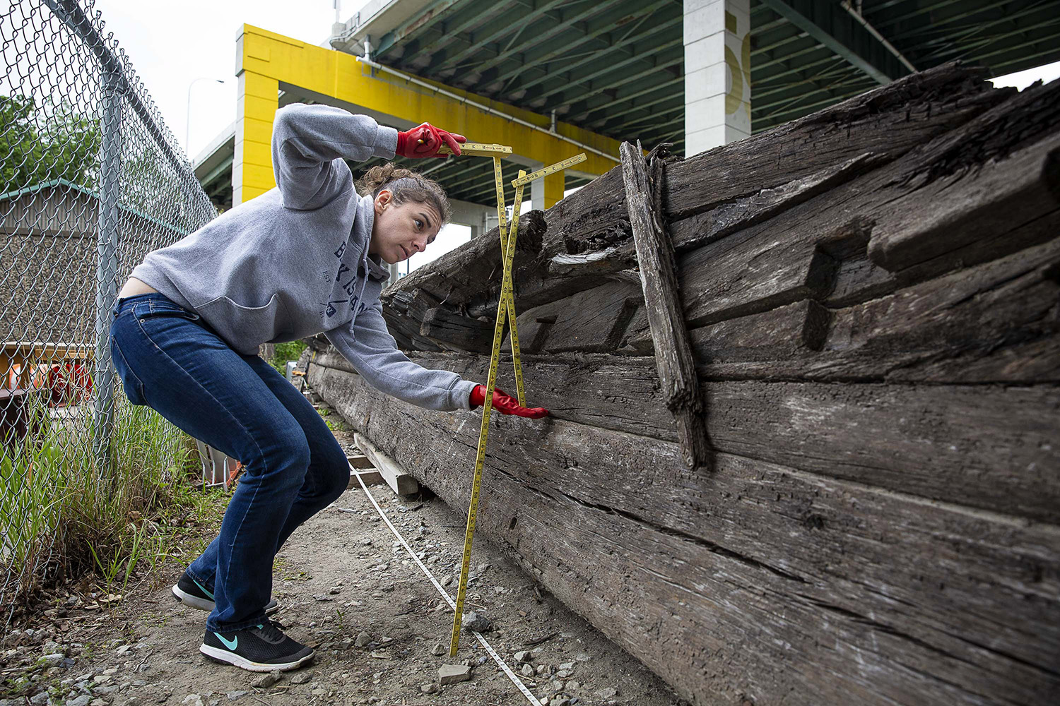 Julia Herbst, a researcher from Texas A&M University, takes measurements of a shipwreck discovered underneath a construction site, Toronto, Wednesday, June 6, 2018.