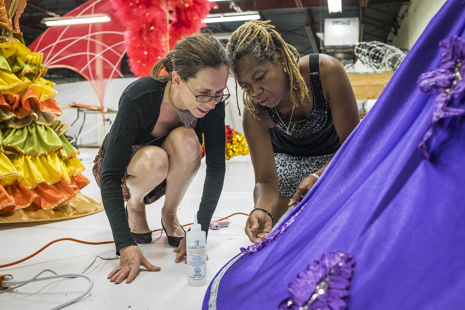 Volunteers Emilsa Sealy (right) and Emily Flude work on the final details of a dress that will be used by a member of the Aristokids section of the Durham Mas, Scarborough, Saturday July 9, 2017.
