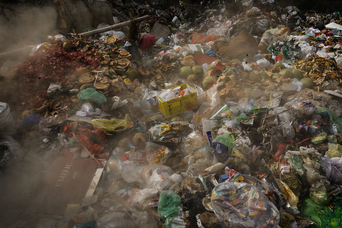 Dust rises as waste is dumped at a garbage collection point in New Delhi, India.