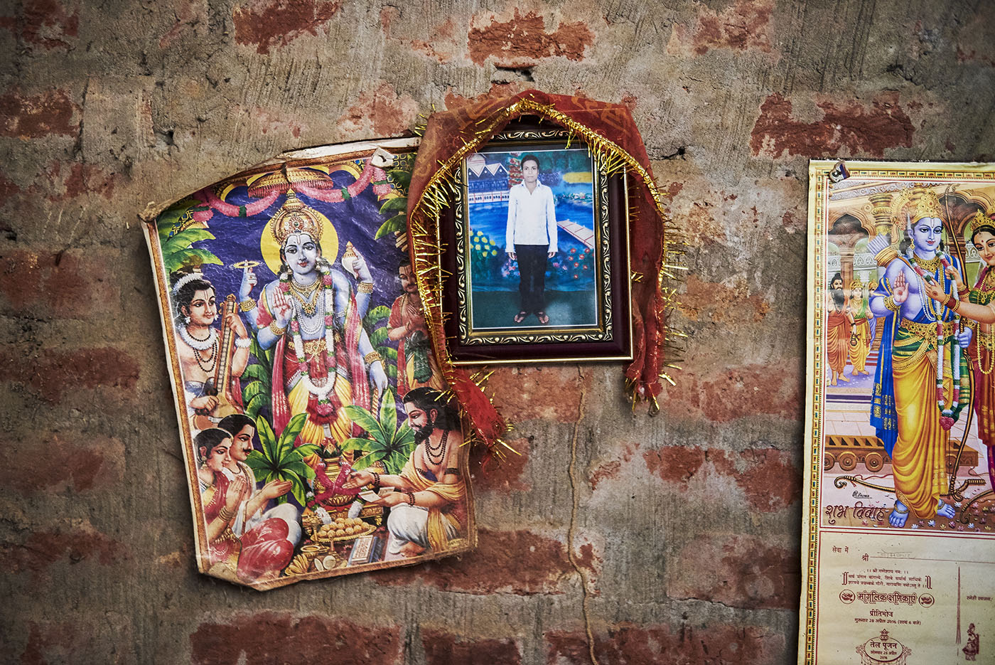 A photograph of Raju is hung along with posters of Hindu Gods. Raju's wife, Reena Devi, prays to them everyday.