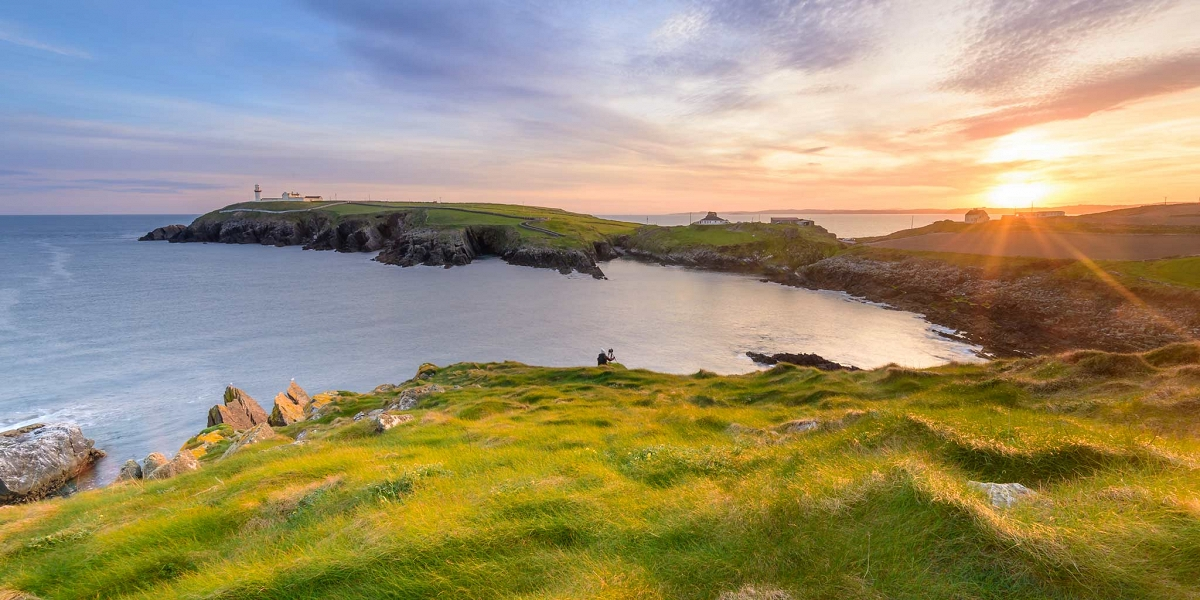 Galley head lighthouse, West Cork, Ireland at sunset being photographed by a tourist