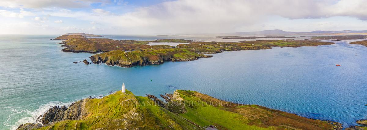 A panoramic photograph of the Baltimore Beacon with Cape Clear and Sherkin islands in the background, West Cork, Ireland