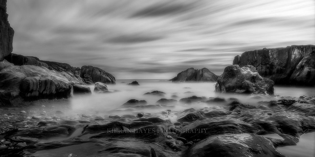 A black and white long exposure photograph with moving clouds over a seascape scene like the images we take on my photography workshops