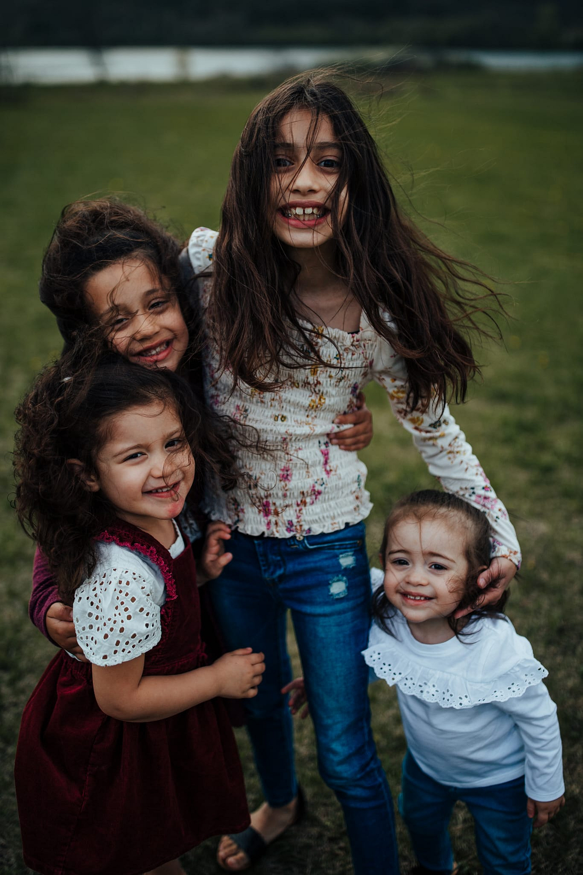 Four young girls stand together smiling as their hair whips in the wind.