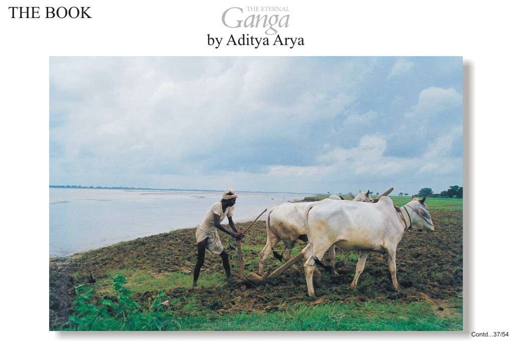 A farmer ploughs his field unmindful of the swollen river.
