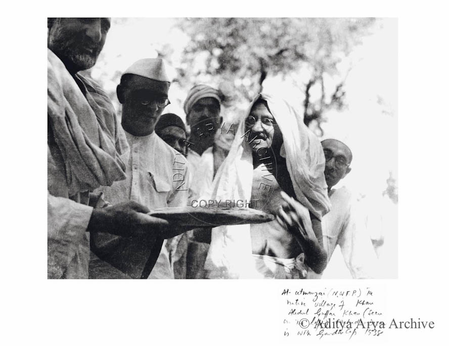 At Utmanzai (NWFP)in native village of Khan Abdul Guffar Khan (seen on left), Mahadev Desai in with Gandhi Cap 1938.