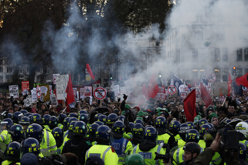 Protesters and police officers clash during a protest against an increase in tuition fees on the edge of Parliament Square in London, Thursday, Dec. 9, 2010.  Police clashed with protesters marching to London's Parliament Square as lawmakers debated a controversial plan to triple university tuition fees in England.