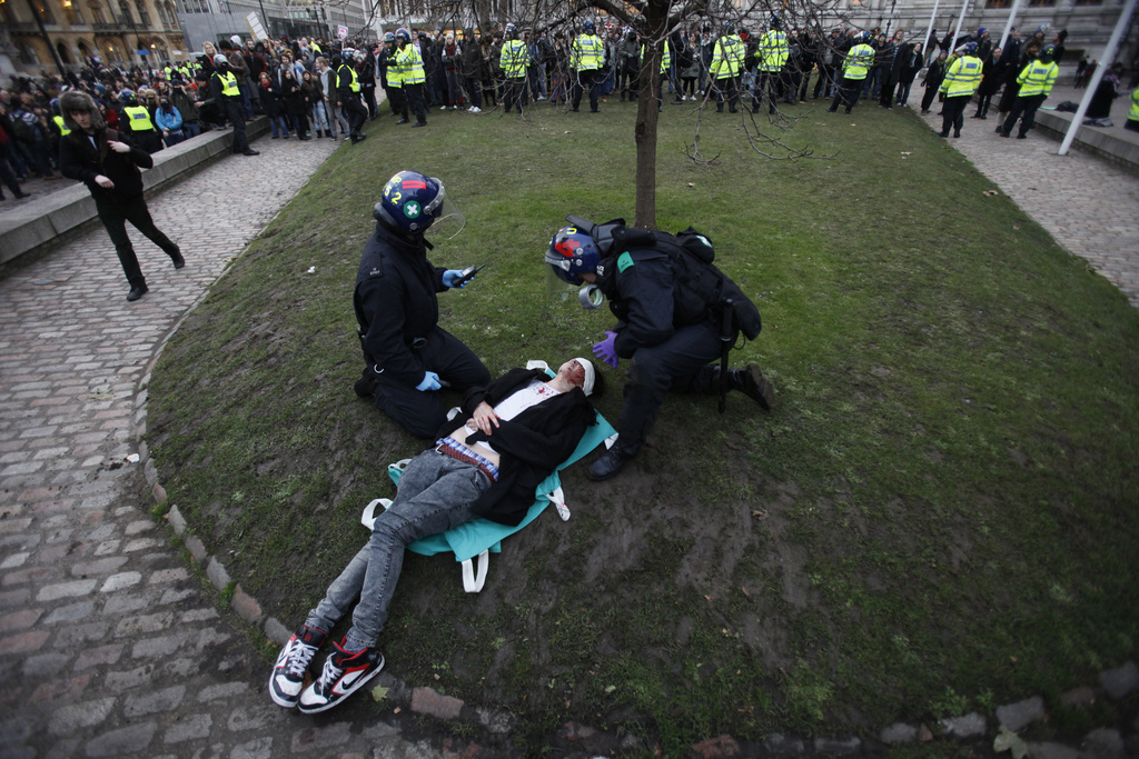 Police medical officers treat an injured protestor during a protest against an increase in tuition fees on the edge of Parliament Square in London, Thursday, Dec. 9, 2010.  Police clashed with protesters marching to London's Parliament Square as lawmakers debated a controversial plan to triple university tuition fees in England
