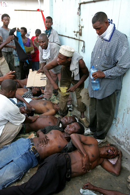 Civic United Front supporters help people overcome by teargas in Stone Town , Tuesday, Nov. 1, 2005 at the party headquaters in Zanzibar.Zanzibari police, backed by soldiers, surrounded the two main opposition party headquarters early Tuesday and marched into at least two other opposition neighborhoods, beating up protesters in a show of forces following disputed weekend elections.
