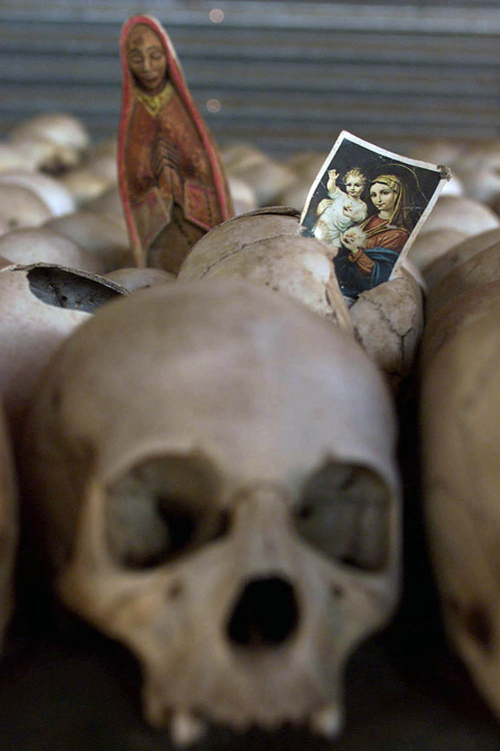 Holy images left by visitors at the skeletal remains of victims of Rwanda's 1994 genocide preserved where they were killed at Ntarama's Roman Catholic Church on Monday, Oct. 1, 2001