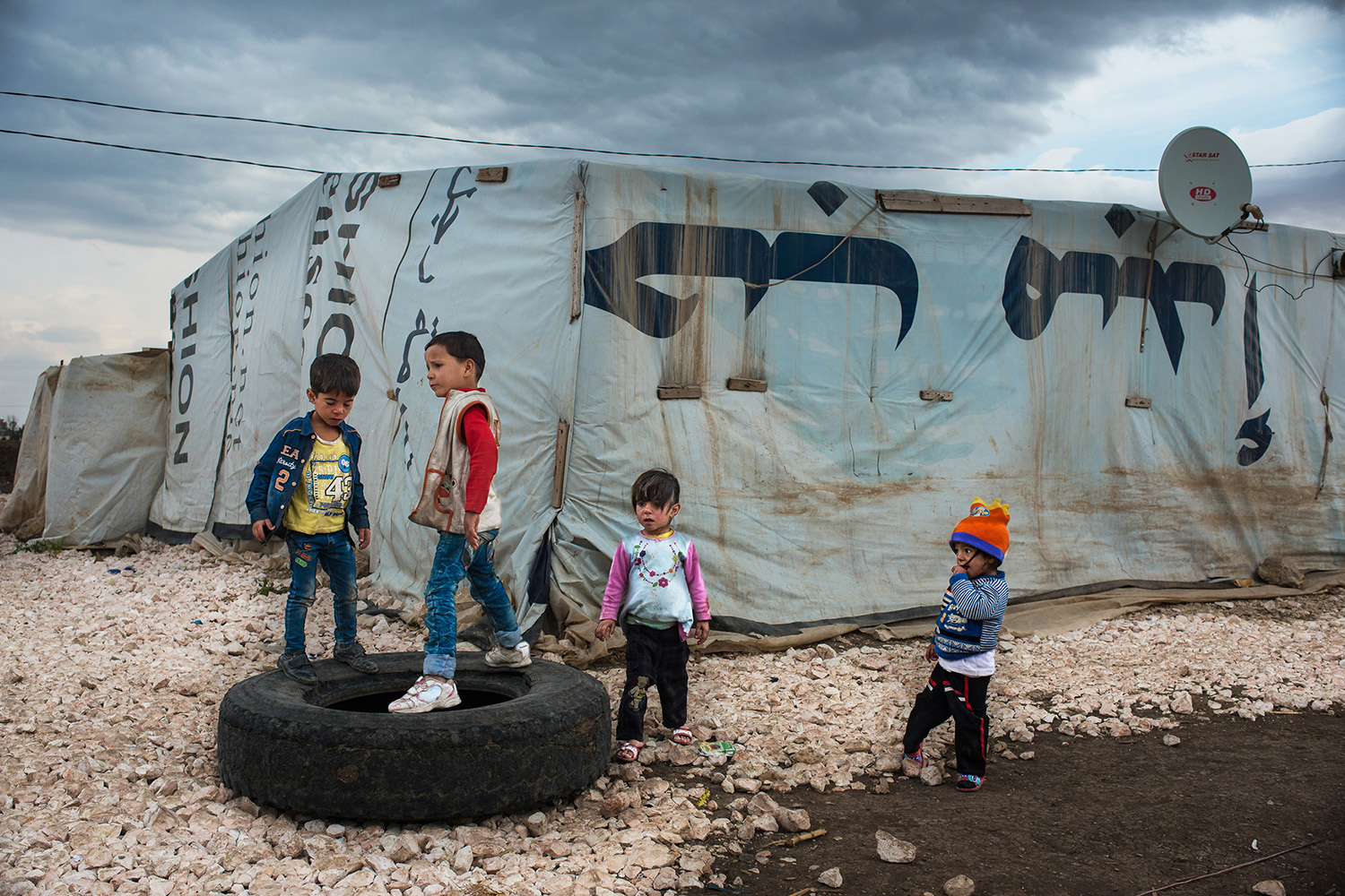 Refugee children playing in a makeshift settlement in the Bekaa Valley, Lebanon, on November 04, 2015. There are almost 1.5 million refugees registered by UNHCR living in Lebanon. A recent report says that 70% of Syrian refugees live bellow the poverty line (U$ 3.84 in Lebanon) and 90% are in debt.