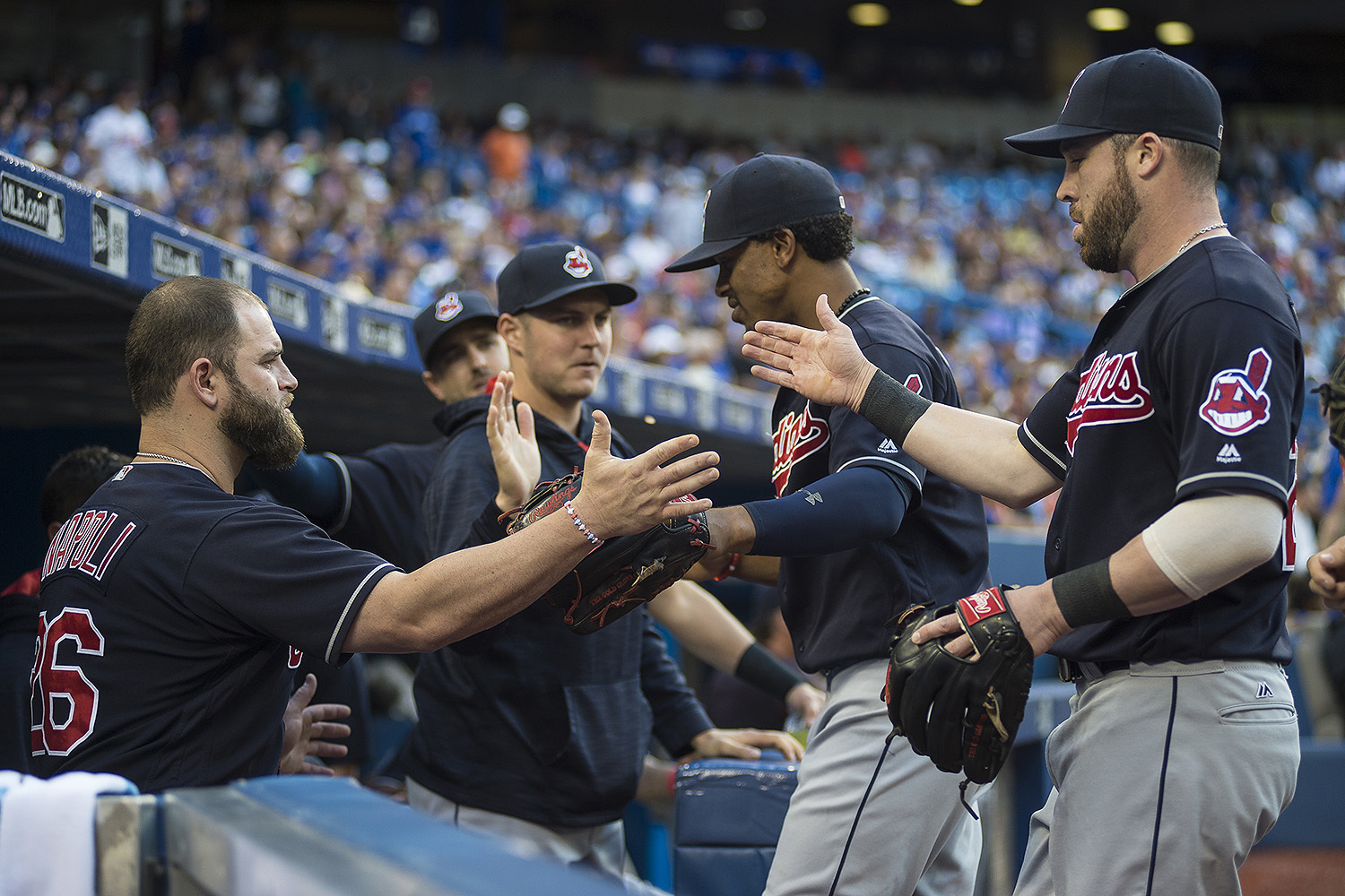 Cleveland Indians' Mike Napoli, left, greets teammates Francisco Lindor, second from right, and Jason Kipnis, right, at the end of first inning against the Toronto Blue Jays, in Toronto, Thursday, June 30, 2016.