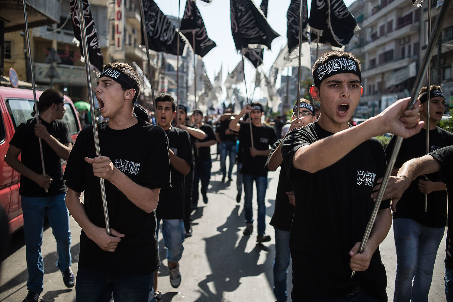 Supporters and members of the Sunni Islamist party Hizb Ut-Tahrir parade through the streets of Tripoli, northern Lebanon, carrying their party's flags and shouting slogans during a rally against Russian and U.S. intervention in Syria.