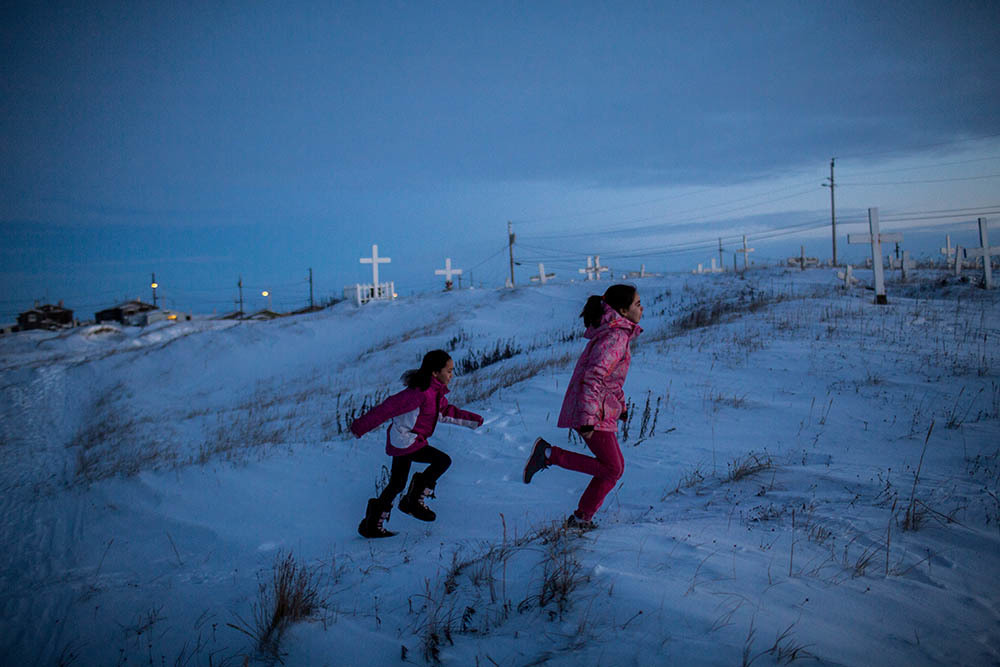 Children play near the the town's cemetery outside the town's only church. Shishmaref is a barrier island with a population of less than 600 Alaska native Inupiaq people located 30 miles south of the Arctic Circle. The island is threatened by global temperature rises which have disproportionately affected the Arctic. Rising water levels and increased erosion mean that Shishmaref is slowly being absorbed by the surrounding seas and the prognosis is that it will disappear completely over the next two decades.